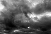 Large textured clouds in black and white for background.