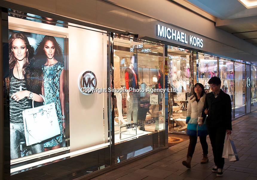 People walk past a newly opened Michael Kors store in Sanlitun, Beijing, China. 11-Jan-2014