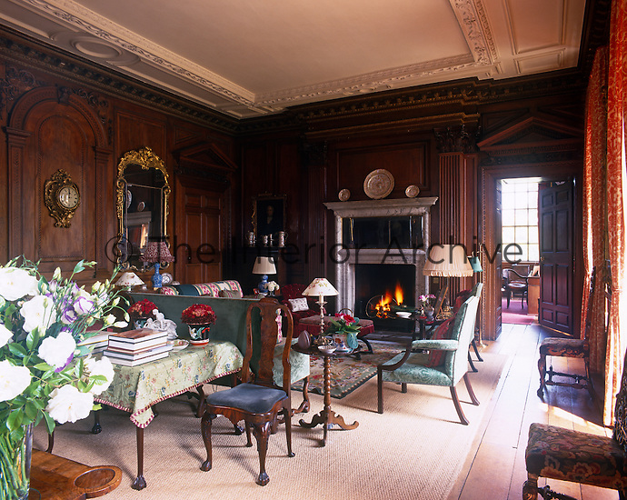 The panelled 18th century drawing room has a marble fireplace and is comfortably furnished