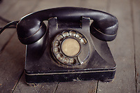 Photo of and old, dusty rotary dial bakelite phone.
