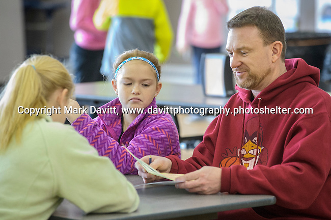 Abigail Hersom, left, her sister Carissa and their father Mark go over their scores at the fourth annual 4th Altoona Elementary Golf in the Halls was held Jan. 28. Participants enjoyed a breakfast and  two, 18-hole mini-golf courses throughout the school's classrooms, hallways and gymnasiums.
