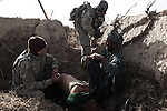 An Afghan man pleads with with counter-IED military contractor and his interpreter after his companion was shot in the back at the beginning of an exchange of fire between soldiers with Charlie Co. 1st Battalion 12th Infantry Regiment, 4th Infantry Division and Taliban fighters on January 27, 2010. Zhari District, Kandahar, Afghanistan. The man received medical aid from US medics on-scene and then later at near-by FOB Wilson. A search of his belongings by Charlie Co. soldiers revealed that the wounded man was in position of a dog-tag belonging to another 1-12 INF soldier killed earlier in the month by an IED strike. The man was subsequently detained. The violently contested district sits astride the strategically Highway 1 ringroad between Kandahar and Lashkar Gah and is seen by some as the birthplace of the Taliban movement.