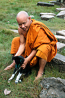 Buddhist monk playing with his dog on the grounds of Bayon, Angkor Thom.