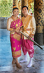 A Lao bride and groom in traditional dress for wedding photos, at the front entrance to Wat Mai Suwannaphumaham in Luang Prabang, Laos.