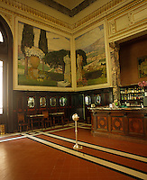 Belle Epoque frescoes by Galileo Chini depicting landscapes cover the walls above the panelled bar at the Tettuccio thermal spa at Montecatini