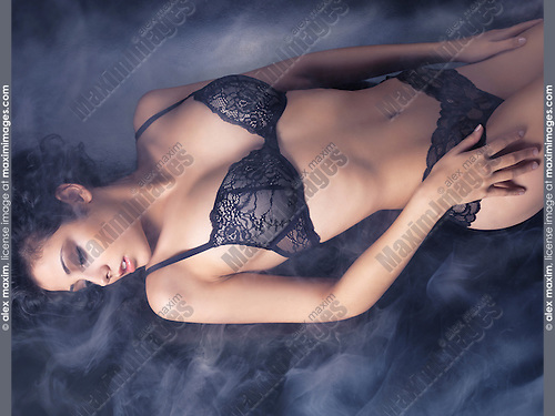 Beautiful sexy young woman in black lacy lingerie lying on the floor in smoke