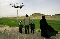 A family from the Iranian city of Shiraz watch as a helicopter carrying President Mahmoud Ahmedinejad to one of his provincial visits lands.