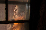 _DSC8589; Thailand; 2007; THAILAND-10025NF3. A monk stands by a dirty window.