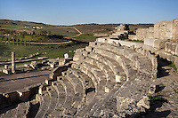 High angle view of from the side of the Theatre, c. 40-60 AD, Segobriga, Spain, pictured on April 13, 2006, in the afternoon. Seating 2,000 people, the raked auditorium surrounds a semi-circular stage. The theatre was decorated with ornate columns and statues whose ruins remain. Segobriga was founded by the Romans in the 1st century BC, after the Punic wars, and the town was developed during the reign of  Augustus. It became an important administrative centre whose local industry was mining 'specularis lapis', a crystallized sheet gypsum used for window glass. Picture by Manuel Cohen.