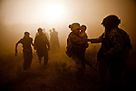 "10/10/2010 Helmand Province, Afghanistan.Flight Medic SGT Ian Bugh (R) of Charlie Co. 6-101st AW links up with a Marine medic carrying an injured Afghan child amid dust kicked up by the Medevac helicopter at a landing zone in southern Helmand Province, Afghanistan...The Helicopter Medevac teams of Task Force Destiny, based at Forward Operating Base Dwyer in Afghanistan's war-torn Helmand Province have a tough job. Servicing a large area that includes still restive southern Marjah, and much of the Helmand River Valley, TF Destiny answers the call to transport gravely wounded US Marines and Afghan civilians from the point of injury in the field to Role 3 trauma centers on bases in the area--often times landing under fire to extract Marines and soldiers that would otherwise succumb to their wounds. After the Medevac helicopter and it's ""chase"" UH-60 Blackhawk companion aircraft get a call, they can be on the ground picking up a patient in as little as 20 minutes--delivering the fallen to a surgical theater within what flight medics refer to as ""the golden hour""--or the hour after a catastrophic injury during which a patients transfer from basic battlefield triage care to a modern trauma surgical unit can mean the difference between life and death. ."