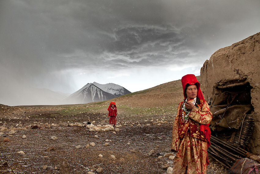 It is late June and two of the Khan's daughter's venture outside their mud hut after a hailstorm at the family's autumn camp beside the Aksu river. The nomads sometimes stop here for a few weeks between migratory seasons if grass for their herds is too scarce at the summer or winter camps...Daily life at the Khan (chief) autumn camp (called Teramo Jai - place of Autumn), beside the Aksu river...Trekking through the high altitude plateau of the Little Pamir mountains (average 4200 meters) , where the Afghan Kyrgyz community live all year, on the borders of China, Tajikistan and Pakistan.