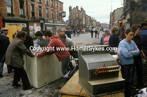 Toxteth Riots Liverpool 1981. Morning after night of riots local men helping themselves. Looting.