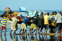 Gambia. Bakau. Atlantic ocean. Bakau is 15 km away from the capital Banjul. Fishermen pull their boat on the beach at sunset.  © 2000 Didier Ruef