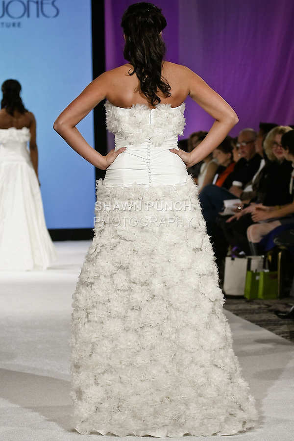 Model walks the runway in Biancospino-201 by AcQuachiara. Dress in silk organdy. Bouquet of big flowers on the small low-necked corset on the full skirt. Wide chiffon drapery at waistline. Romantic poetry. During the Wedding Trendspot Press Fashion Show at the Waldorf-Astoria; October 18 2009