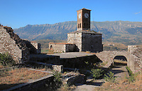 The Clock Tower, erected 19th century by Ali Pasha, at the Kalaja e Gjirokastres or Gjirokastra Castle, built before the 12th century and expanded by Ali Pasha of Tepelene after 1812, Gjirokastra, Albania. The castle dominates the town and overlooks the strategically important route along the river valley. The government of King Zog expanded the castle prison in 1932. Today it has 5 towers and houses, the new Gjirokastra Museum, a clock tower, a church, a cistern and the stage of the National Folk Festival. Gjirokastra was settled by the Greek Chaonians, the Romans and Byzantines before becoming an Ottoman city in 1417. Its old town was listed as a UNESCO World Heritage Site in 2005. Picture by Manuel Cohen