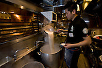 Store manager Yusuke Osako prepares the soup in the kitchen at Hakata Ippudo Ramen's main store in the Daimyo district of Fukuoka City, Fukuoka Prefecture Japan on 08 March 2013.  Photographer: Robert Gilhooly