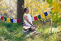 Man in yoga posture outdoors in the forest.