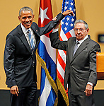 After the two presidents shake hands Cuban President Raul Castro lifts President Obama's arm after delivering speeches at the Palacio de la Revolucion in Havana on Monday, March 21, 2016.