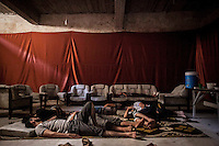 Syrian civilians and opossition fighters sleep as they take refugee from daily shelling during night inside a basement building at Anadan village, in northern Aleppo.