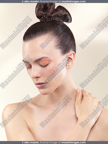 Beauty portrait of a young woman with closed eyes wearing soft pastel color makeup and beautiful hairstyle