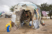 Somaliland. Waqohi Galbed province. Gabiley. A mother, black muslim woman wearing a veil on the head, seats inside a traditional somali hut and holds a child in her arms. Another daughters sits nearby. Plastic jerrycans blue and yellow used as water containers. Somaliland is an unrecognized de facto sovereign state located in the Horn of Africa.  © 2006 Didier Ruef