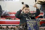 Foto: VidiPhoto<br /> <br /> SLIJK-EWIJK - Fruitteler Frederik Bunt uit Slijk-Ewijk is maandag gestart met het zelf enten van 21.000 onderstammen voor nieuwe pruimenbomen. Volgend jaar volgt nog eens eenzelfde aantal. Omdat de kwaliteit van de pruimenbomen van Nederlandse boomkwekers volgens de Betuwse teler ver onder de maat is, probeert hij het na acht jaar overleg met de kwekers nu zelf. Daarbij wordt de grootste pruimenteler van ons land geholpen door  familie en Poolse werknemers. Op de eerste entdag krijgen de mannen les van Ian Adams (55) uit Nieuw-Zeeland en zijn Europese compagnon Manuel Alisch (22) uit Duitsland met een nieuw en handig entsysteem -een mini-guillotine- waarmee zelf enten vrij simpel wordt. De beiden mannen trekken door Europa om het systeem te promoten. De ge&euml;nte stammen gaan eerst bijna twee jaar in de pot in een plastic tunnel, alvorens ze op 9 ha. nieuwe pruimenboomgaard worden geplant. Met meer pruimen en nieuwe soorten wil Bunt het pruimenseizoen verlengen naar 8-10 weken. Foto: Het aanbrengen van entwas tegen uitdrogen van de stammetjes.