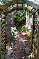 Wooden arbor trellis entryway with mulched pathway, stones, hostas, shade garden side of house, trees.