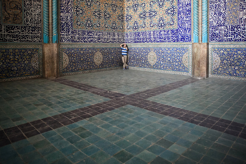 A tourist takes photographs of the interior of Sheikh Lotfollah Mosque. Sheikh Lotfollah Mosque is one of the architectural masterpieces of Safavid Iranian architecture, standing on the eastern side of Imam Square (Naqsh-E Jahan), Isfahan, Iran..Construction of the mosque started in 1603 and was finished in 1618. It was built by the chief architect Shaykh Bahai, during the reigh of Shah Abbas I of the Safavid dynasty..It is registered, along with the Imam Square, as a UNESCO World Heritage Site.