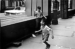 MANHATTAN , NEW YORK,  USA  JUNE 1969: YOUNG BOY HOLDS UP AN OPEN KNIFE AS IF TO ATTACK ANOTHER CHILD WHO IS RUNNING AWAY. Two juvenile males play knife blade fight pretend throw terror acting like adults street crime terrorises fear fun  black and white candid reportage street scene