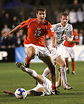 14 December 2007: Virginia Tech's Scott Dillie (22) jumps over Wake Forest's Cody Arnoux (below) as Pat Phelan (5) follows the play. The Wake Forest University Demon Deacons defeated the Virginia Tech University Hokies 2-0 at SAS Stadium in Cary, North Carolina in a NCAA Division I Men's College Cup semifinal game.