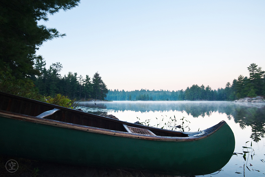 Morning dawns over a green canvas canoe pulled up on misty shores of Balsam Lake on a clear summer day.