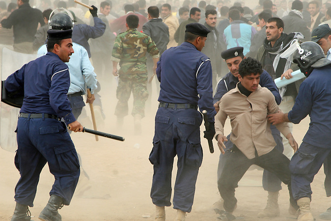 Police help a man who has been injured during a melee at a police recruiting drive in Kirkuk, Iraq. Officials sought to fill 1,300 slots for the next training class, but were overwhelmed when more than 4,000 applicants showed up. Hundreds of them waited in line for hours, but never got a chance to submit their papers.The event was shut down after a U.S. advisor observed an Iraqi recruiting officer take a bribe from an applicant. Desperate job seekers were ordered to disperse, but many refused, so police resorted to violence to force them from the grounds. Dec. 6, 2007. DREW BROWN/STARS AND STRIPES