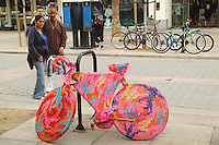 A couple look at &quot;Bike-like object no. 9&quot; by Polish artist Olek at the Third Street Promenade on Friday, October 15, 2010.