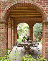 The loggia features brick archways and an al fresco dining area