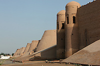 Low angle view of South Gate, Tash Darvaza (Stone Gates), and walls of the old city, Khiva, Uzbekistan, pictured on July 7, 2010, at dawn. Khiva's old city, Ichan Kala, is surrounded by 2.2 kilometres of crenellated and bastioned city walls. Some sections may be 5th century, but the strongest sections were built 1686-88 by Arang Khan. The Tash Darvaza was built in the 19th century during the reign of Allakulykhan. Khiva, ancient and remote, is the most intact Silk Road city. Ichan Kala, its old town, was the first site in Uzbekistan to become a World Heritage Site(1991). Picture by Manuel Cohen.