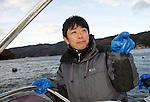 Takeshi Tachibana of Oh! Guts! stands aboard a fishing boat in Ogatsu Bay, Ishinomaki, Miyagi Prefecture, Japan on 01 Dec 2011. .Photographer: Robert Gilhooly
