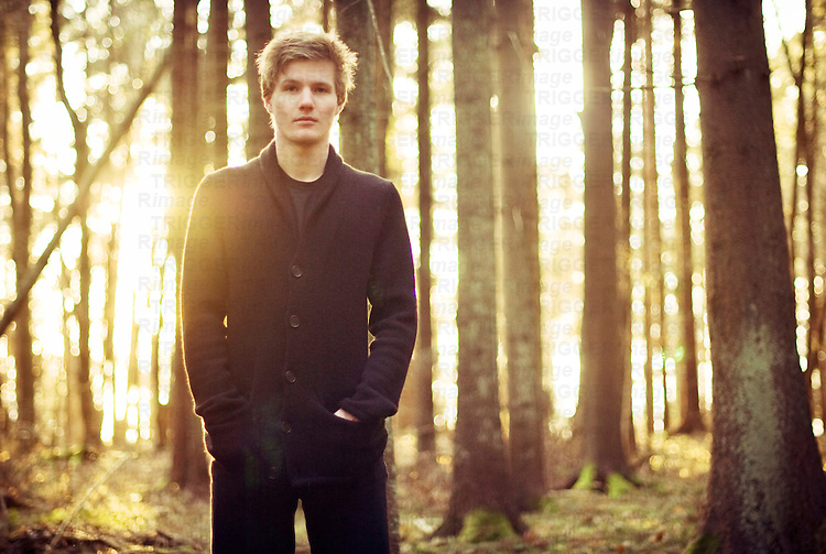 Picture of young man standing in a forest at sunset looking into the camera