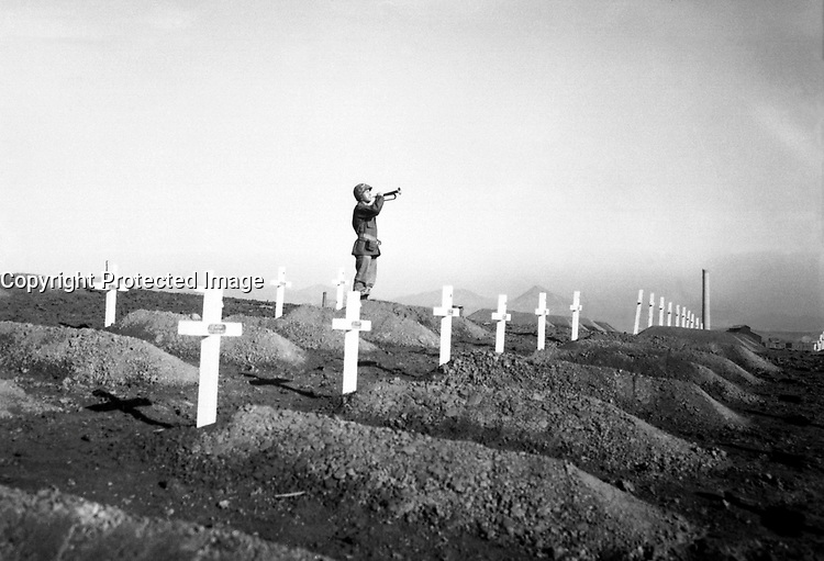 Cpl. Charles Price sounds &quot;Taps&quot; over the graves of fallen Leathernecks during memorial services at the First Marine Division cemetery at Hungnam, following the division's heroic break-out from Chosin Reservoir.  December 13, 1950.  Cpl. W. T. Wolfe. (Marine Corps)<br /> NARA FILE #:  127-N-A5421<br /> WAR &amp; CONFLICT BOOK #:  1513