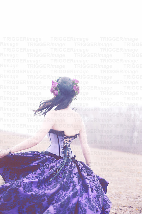 The back of a young brunette female with flowers in her hair, twirling with motion, wearing a purple corset gown outdoors