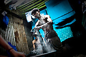 Men are seen dyeing clothes in a make shift shack in Dharavi, the slums in Mumbai, India