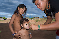 Xingu Indian children being being given oral vitamin supplements, Amazon Basin, Brazil.