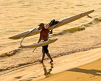 An avid waterman carries his one-man canoe to the waters of Kailua Beach