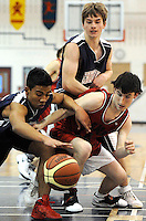 Ian Stewart/Yukon News<br /> Vanier Crusaders Belgie Nunez, left, and Jon Koltun scramble for a loose ball with Porter Creek's Matt McCarthy, right, during a Yukon Basketball Championships preliminary game on Thursday at Vanier Catholic Secondary School. Vanier won the game 86-37.