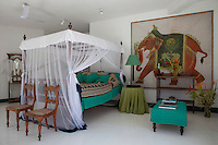 A large batik of a decorated elephant hangs next to a four-poster bed draped with a mosquito net