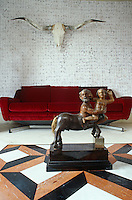 The skull  of a long-horn cattle hangs above a red velvet sofa facing the sculpture of a centaur on the coffee table in the living room