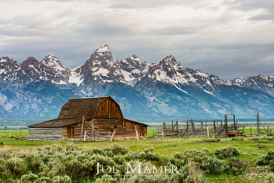 The John Moulton Barn at sunrise with rainbow on Mormon Row against the Teton Range Mountains in Grand Teton National Park.