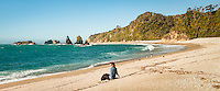 Young woman on beautiful remote beach in South Westland, UNESCO World Heritage Area, West Coast, New Zealand, NZ
