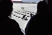 An airport police K-9 unit conducts training exercises with one of its bomb sniffing dogs while travelers look on from a nearby terminal walkway, May 25, 2007, in Dallas, Texas.