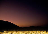 Stars in a dusk sky over the sand dunes of the Namib-Naukluft Park illuminated by car headlights, near Swakopmund, Namibia, Africa