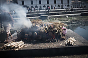 A priest prepares the pyre for the dead while the family members wait next to it outside the Pashupathi Nath Temple in capital Kathmandu, Nepal